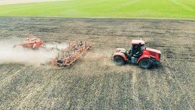 Den röda traktoren med en släp är på ett fält som arbetar lager videofilmer