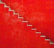 Den röda väggen med trappa texturerar bakgrund, minimalistic stil Royaltyfri Foto
