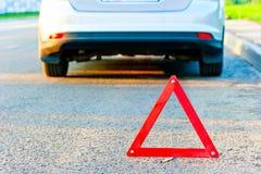Den röda varningstriangeln och en bil drar över till sidan av vägen arkivfoton