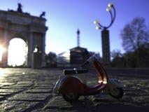 Den röda vespaen parkerade framme av den arco dellahastigheten Milan Italy Arkivfoton