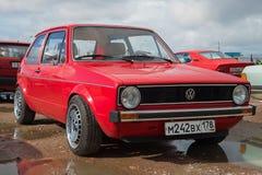 Den röda Volkswagen Golf första utvecklingen (1973 modellerar år), på utställningen och ståtar av tappningbilar Royaltyfri Foto