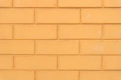 Den rödaktiga gula texturen för tegelstenvägg Royaltyfria Foton