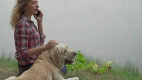 Den rödhårig mankvinnan och hunden vilar nära vattnet tillsammans arkivfilmer