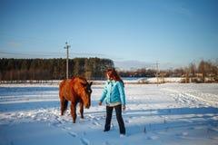 Den rödhåriga flickan går med en häst i ett snöig fält arkivbilder
