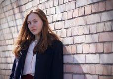 Den rödhåriga flickan står nära en tegelstenvägg arkivbild