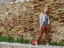 Den rödhåriga flickan står nära en tegelstenvägg, hipster Royaltyfria Bilder