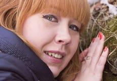 Den rödhåriga flickan trycker på mossan på stenen Fotografering för Bildbyråer