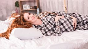 Den rödhåriga gravida kvinnan ligger i en hemtrevlig säng royaltyfri bild