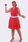 Den rödhåriga kvinnan i röd klänning 60 år utformar, och fetma, poserar med en muffin Arkivfoto