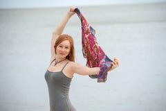 Den rödhåriga kvinnan rymmer upp en sjal Royaltyfri Fotografi