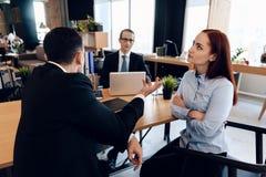 Den rödhåriga missbelåtna kvinnan, med hennes händer som tillsammans knäppas fast, lyssnar till mannen i dräkt i kontor för advok arkivbilder