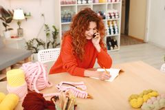 Den rödhåriga needlewomanen som drar något, skissar för framtida arbete Fotografering för Bildbyråer