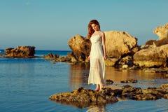 Den rödhåriga sinnliga flickan i ett vitt klänninganseende på havet Arkivfoto