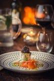 Den rökte laxen med ost, löken och örter tjänade som på plattan med exponeringsglas av vin och rostat bröd, modern gastronomi royaltyfri fotografi