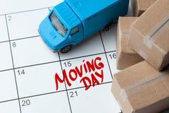 Den rörande dagen på kalendern är skriftlig i rött Kalender med en anmärkning med kartonger och lastbilen royaltyfria foton
