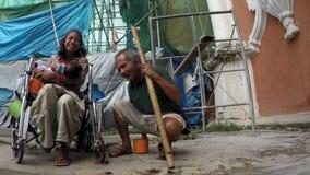 Den rörelsehindrade damen som tiggaren på rullstolkel behandla som ett barn flickan på den kyrkliga portalen, fördärvar stock video