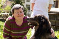 Den rörelsehindrade kvinnan är smekningen per hund royaltyfria foton
