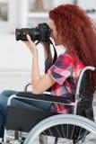 Den rörelsehindrade kvinnan i rullstol har passion för fotografi Fotografering för Bildbyråer