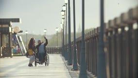Den rörelsehindrade mannen i en rullstol tar bilder av den unga kvinnan på kajen stock video