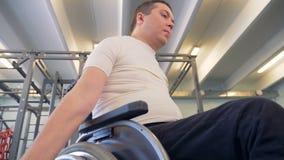 Den rörelsehindrade mannen ser hans hållande hantel för handen under att öva arkivfilmer