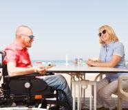 Den rörelsehindrade mannen sitter med en kvinna arkivbilder