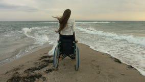 Den rörelsehindrade personen får ut ur sittvagnen på kusten av havet stock video
