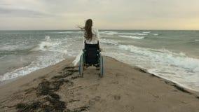 Den rörelsehindrade personen får ut ur sittvagnen på kusten av havet arkivfilmer