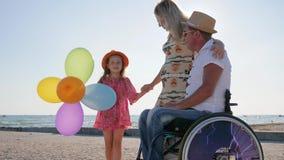 Den rörelsehindrade personen i rullstol med familjen, moderskap, liten flicka lyssnar modern och fadern på stranden i sommartid arkivfilmer