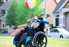 Den rörelsehindrade pojken som slår bollen med slagträet på, parkerar Arkivbild