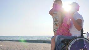 Den rörelsehindrade rullstolanvändaren med familjen, modershowhand till himmel på havskust, uppfostrar med barnet på vilar, lyckl lager videofilmer
