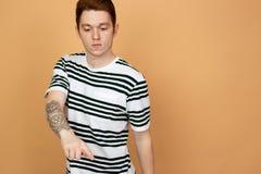 Den r?dh?riga stilfulla grabben i en randig skjorta med tatueringen p? hans hand poserar p? den beigea bakgrunden i studion royaltyfria bilder