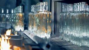 Den raka raden av kristall-rengöringen glasflaskor fortskrider transportören till och med brand och får förflyttad från den arkivfilmer