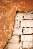 Den rappade halvan red ut tegelstenväggen mycket kopieringsutrymme sprucken vägg Åldrig arkitekturdetalj Halv Grungetegelstenvägg Arkivbild