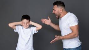 Den rasande farsan som skriker på hans son, det förskräckta barnet, stänger hans ögon och öron arkivbild