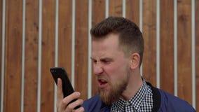 Den rasande mannen ropar i mobiltelefonen som svär med interlokutören, närbilden arkivfilmer