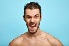Den rasande shirtless mannen visar negativa sinnesrörelser, känsla som isoleras över blå bakgrund arkivbilder