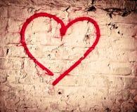 Den röda förälskelsehjärtahanden som drogs på grunge för tegelstenvägg, texturerade bakgrund Arkivbild