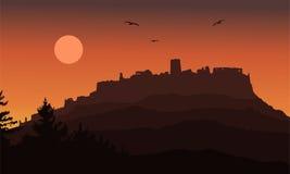 Den realistiska konturn av fördärvar av en medeltida slott som byggs på en kulle utöver skogen under en dramatisk himmel med måne Arkivfoton