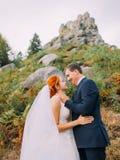 Den Redhair bruden med den lyckliga brudgummen ser lovingly de på steniga Carpathian berg för bakgrund Royaltyfria Bilder