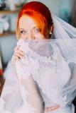 Den Redhair flickan i en bröllopsklänning täcker framsidan skyler förbi Ljust utseende, studioinrebakgrund arkivbild