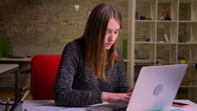 Den Redheaded caucasian unga kvinnan som i regeringsställning sitter, får inblick och startar att arbeta intensivt arkivfilmer