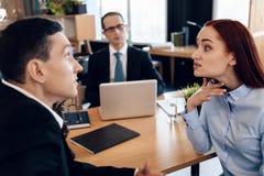 Den Redheaded ilskna kvinnan argumenterar med den vuxna mannen i kontor för ` s för skilsmässaadvokat Royaltyfri Foto