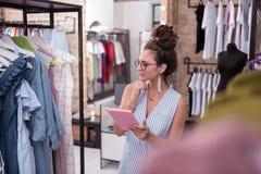 Den reflekterande kvinnlign shoppar assistenten som studerar nya ankomster royaltyfri bild