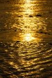 Den reflekterande soluppgången ytbehandlar på floden Arkivbild
