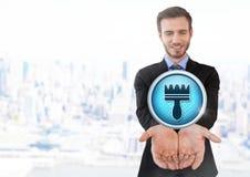 Den rena den borstesymbolen och affärsmannen med händer gömma i handflatan öppet i stad Royaltyfri Bild