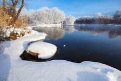 Den rena vita snön vid flodstranden Fotografering för Bildbyråer