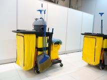 Den rengörande hjälpmedelvagnen väntar på lokalvård Ösregna och uppsättningen av lokalvårdutrustning i kontoret janitorial dörrva Royaltyfri Bild