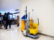 Den rengörande hjälpmedelvagnen väntar på lokalvård Ösregna och uppsättningen av lokalvårdutrustning i varuhuset royaltyfria foton