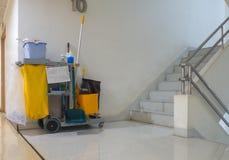 Den rengörande hjälpmedelvagnen väntar på rengöringsmedlet Hink och uppsättning av rengörande utrustning i lägenheten dörrvaktser arkivbilder