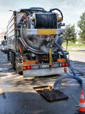 Den rengörande lastbilen pumpar ut vattenavrinningen Fotografering för Bildbyråer